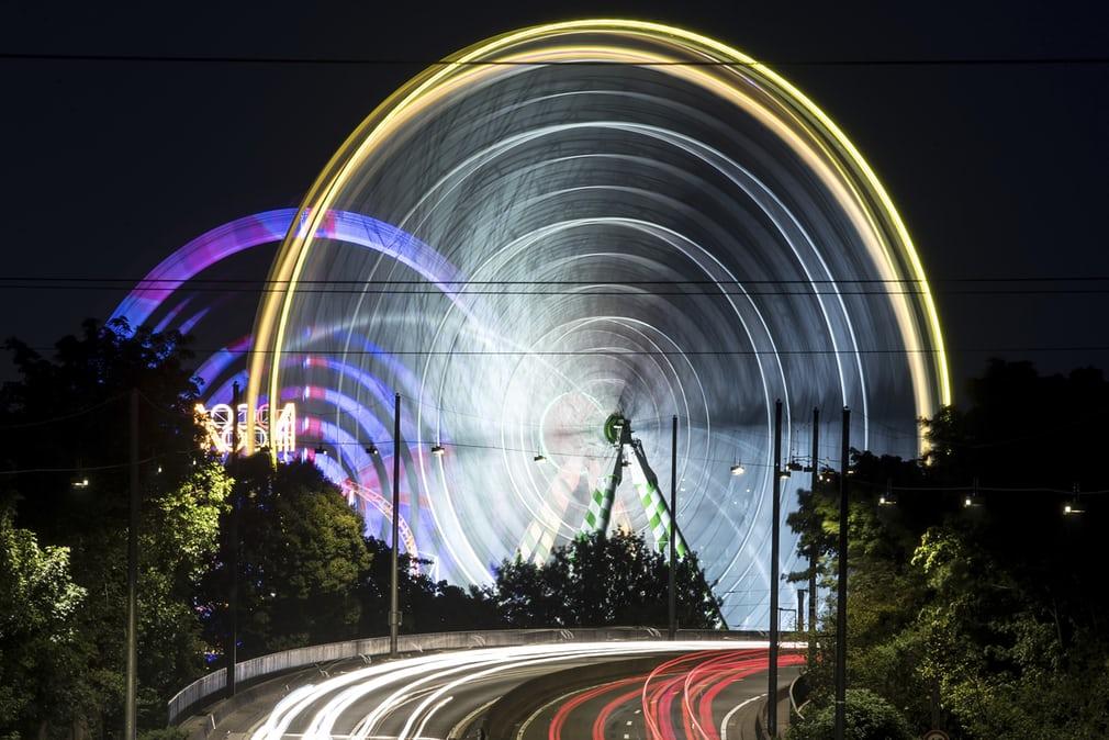 Фотография трассы рядом с парком аттракционов и колеса обозрения с длинной выдержкой.Дюссельдорф, Германия.
