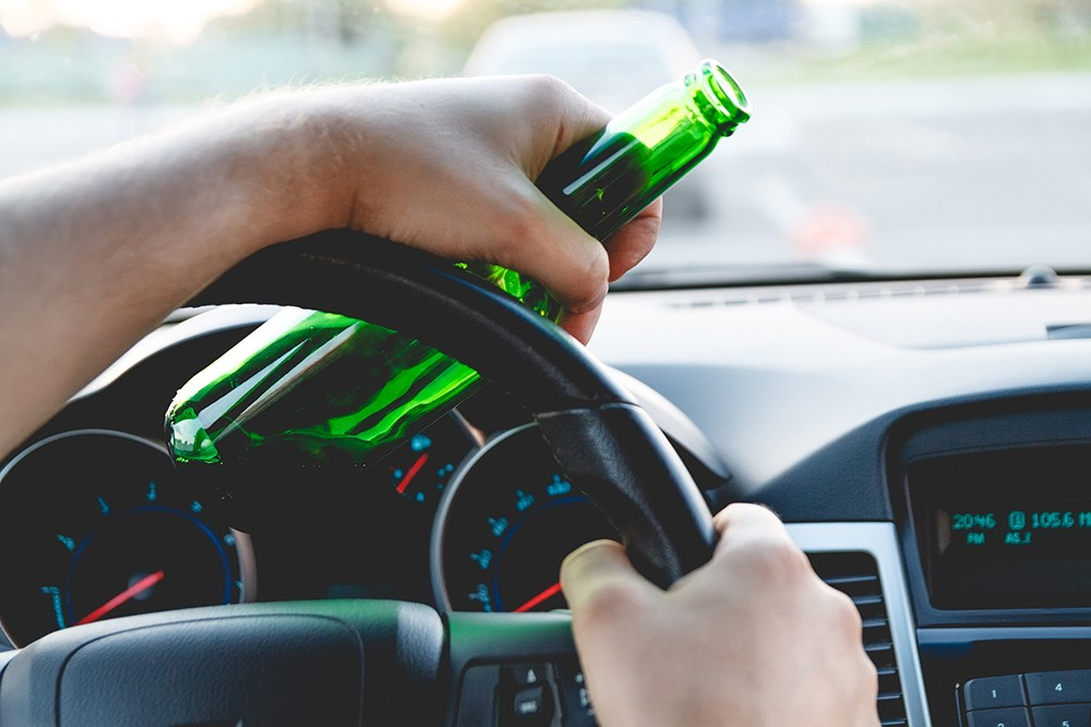 пьяный водитель за рулем с бутылкой