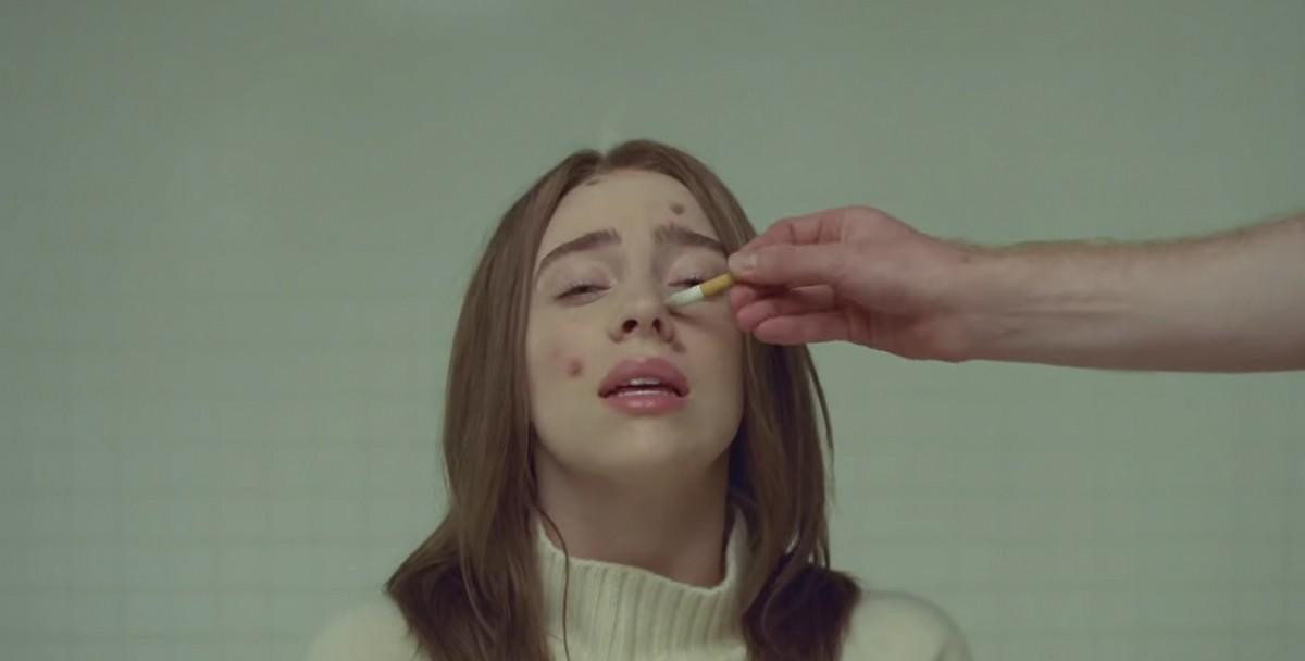 Билли Айлиш выпустила клип, в котором о ее лицо тушат окурки