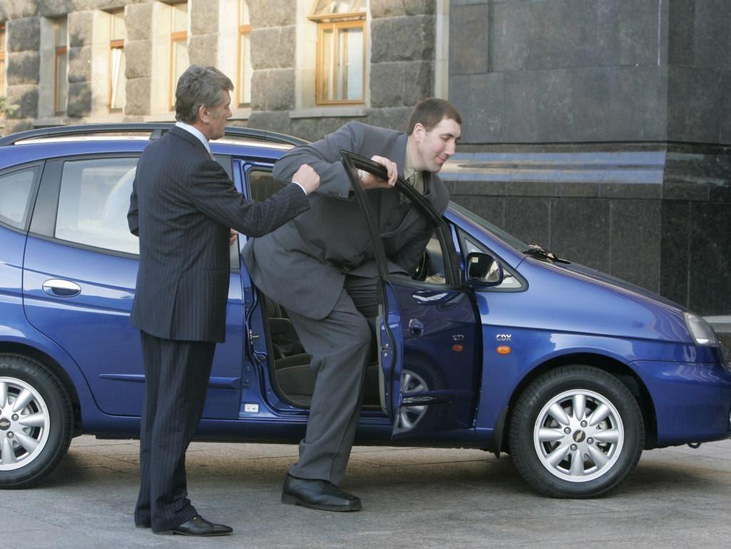 Высокий человек садиться в маленькую машину