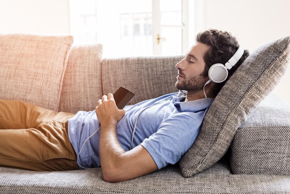 мужчина слушает музыку на диване