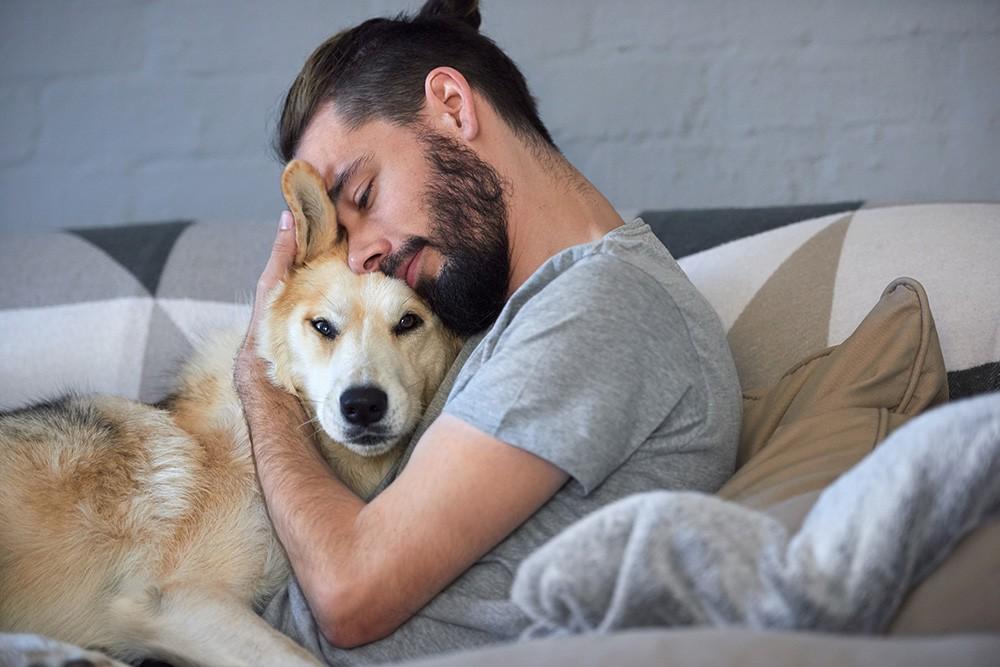 мужчина собаку обнимает